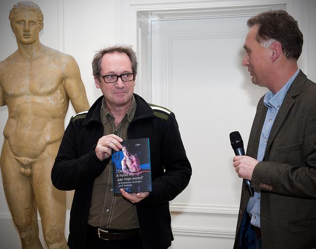 Gijs Scholten van Aschat neemt eerste exemplaar in ontvangst van 'Demetrius, ik houd mij aan mijn woord' van Wim Huijser.